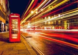 London red telephone box static next to timelapse blurred lights at night